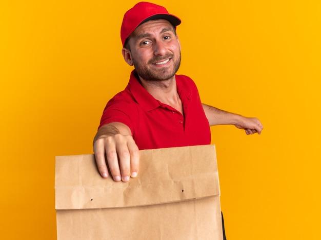 주황색 벽에 격리된 카메라를 향해 종이 패키지를 쭉 뻗고 있는 카메라를 바라보며 프로필 보기에 서 있는 모자와 빨간 유니폼을 입은 웃고 있는 젊은 백인 배달원