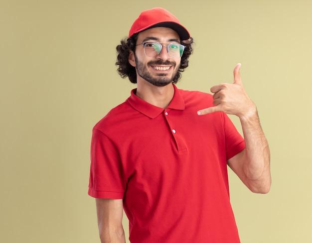 웃는 젊은 백인 배달원은 빨간 유니폼을 입고 안경을 쓴 모자를 쓰고 올리브 녹색 벽에 복사 공간이 있는 느슨한 몸짓을 하고 있다