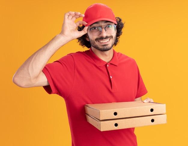 Улыбающийся молодой кавказский курьер в красной форме и кепке в очках, схватив кепку с упаковками пиццы, изолированными на оранжевой стене