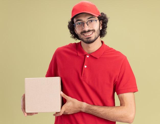 赤い制服を着て、カードボックスを保持している眼鏡をかけて帽子をかぶった若い白人配達人の笑顔