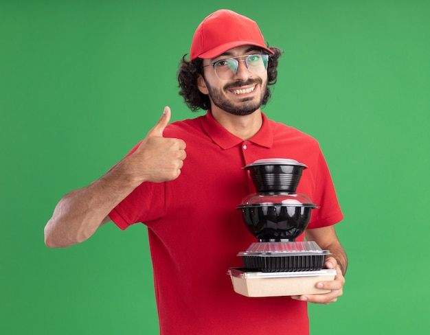 赤い制服を着た若い白人配達人の笑顔と、緑の壁に隔離された親指を示す紙の食品パッケージと食品容器を保持している眼鏡をかけた帽子