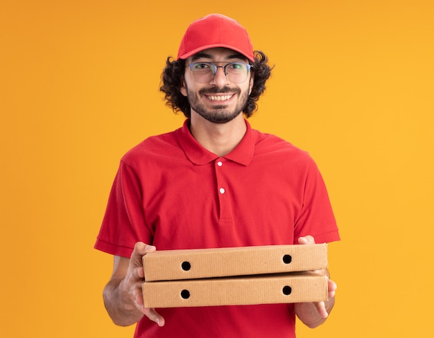 주황색 벽에 격리된 피자 패키지를 들고 안경을 쓰고 빨간 유니폼을 입은 백인 젊은 배달원