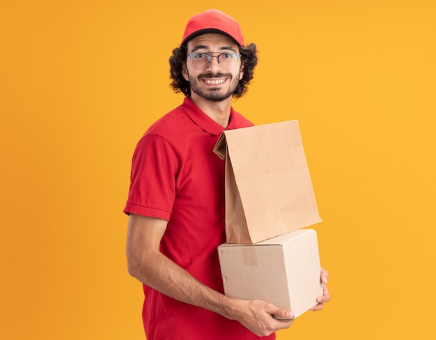 빨간색 제복을 입은 젊은 백인 배달 남자와 모자를 쓰고 프로필보기에 서있는 안경을 쓰고 종이 패키지와 함께 cardbox를 앞에보고 웃고