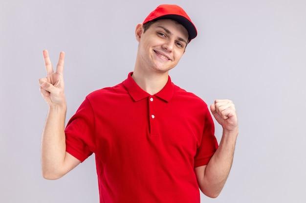 Sorridente giovane fattorino caucasico in camicia rossa che tiene il pugno e gesticola il segno della vittoria