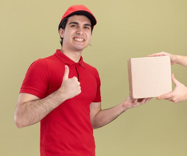 Sorridente giovane fattorino caucasico in uniforme rossa e cappuccio che dà cardbox al cliente che mostra pollice in su isolato su parete verde oliva