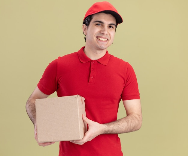 Smiling young caucasian delivery man in red uniform and cap holding cardbox isolated on olive green wall