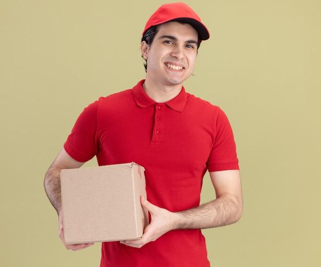 Sorridente giovane caucasico fattorino in uniforme rossa e cappuccio che tiene scatola di cartone isolato su parete verde oliva