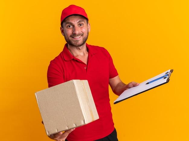 Sorridente giovane fattorino caucasico in uniforme rossa e cappuccio che tiene appunti che allungano la scatola di cartone verso la telecamera