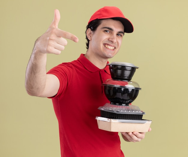 Smiling young caucasian delivery man in red uniform and cap holding food containers and paper food package looking and pointing  isolated on olive green wall