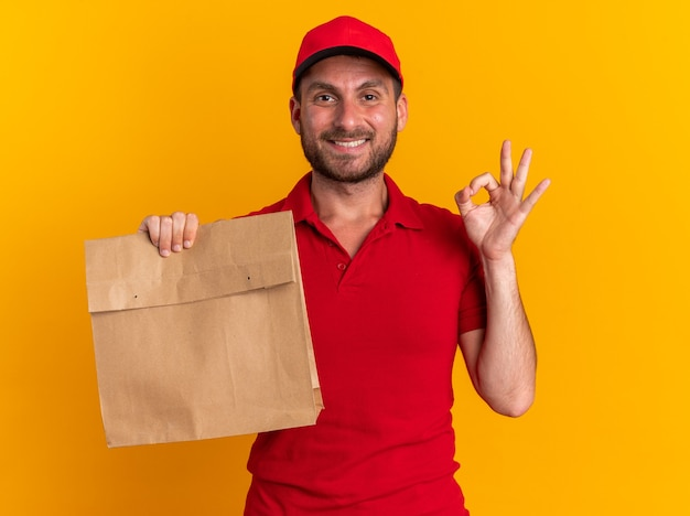 Sorridente giovane fattorino caucasico in uniforme rossa e berretto con in mano un pacchetto di carta guardando la telecamera facendo segno ok isolato sul muro arancione