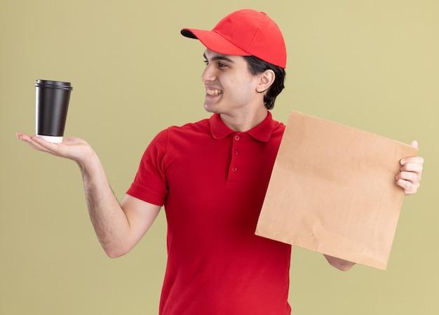 Sorridente giovane fattorino caucasico in uniforme rossa e berretto con in mano un pacchetto di carta e una tazza di caffè in plastica che guarda la tazza di caffè