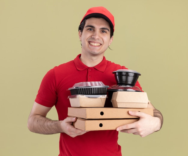 Smiling young caucasian delivery man in red uniform and cap holding pizza packages with food containers and paper food packages on them  isolated on olive green wall