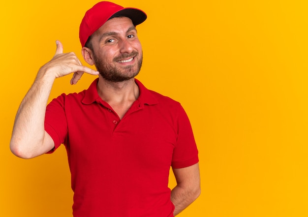 Smiling young caucasian delivery man in red uniform and cap keeping hand behind back doing call gesture