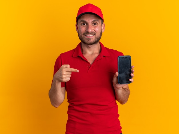 Smiling young caucasian delivery man in red uniform and cap looking at camera showing mobile phone pointing at it isolated on orange wall