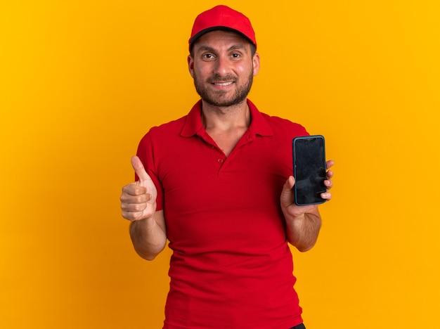 Smiling young caucasian delivery man in red uniform and cap looking at camera showing mobile phone and thumb up isolated on orange wall