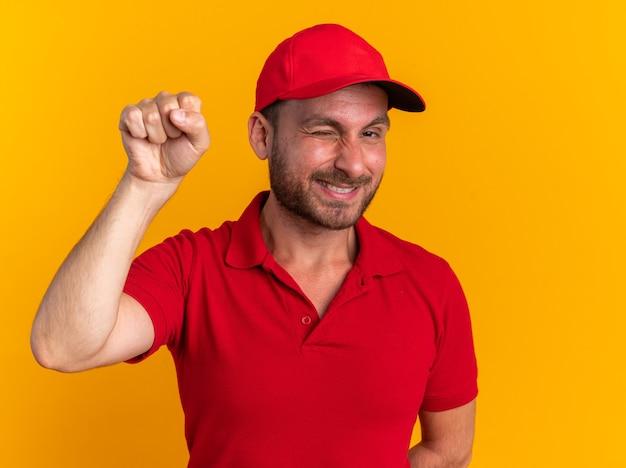 Sorridente giovane fattorino caucasico in uniforme rossa e berretto che guarda l'obbiettivo che fa l'occhiolino facendo un gesto di bussare isolato sul muro arancione