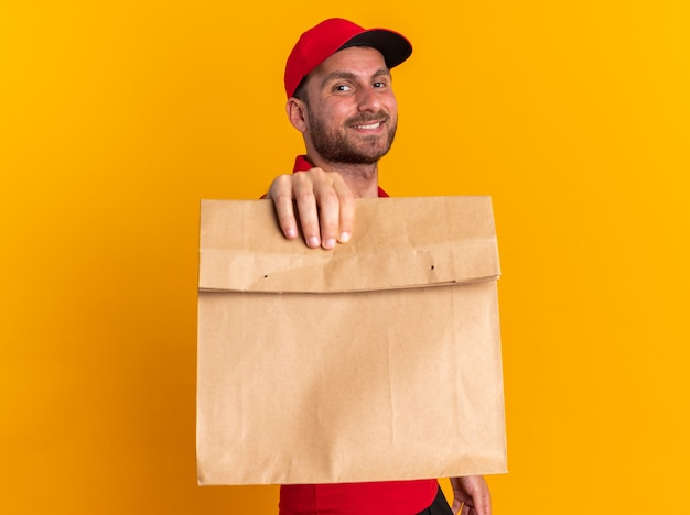 Smiling young caucasian delivery man in red uniform and cap standing in profile view looking at camera stretching out paper package towards camera isolated on orange wall