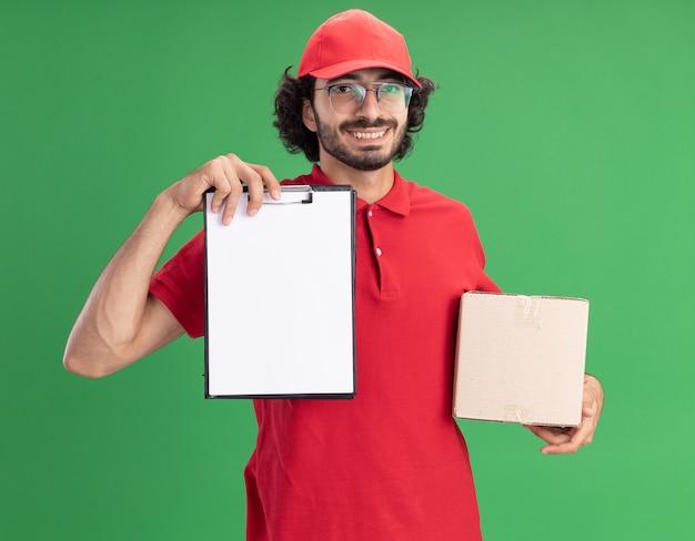 Sorridente giovane fattorino caucasico in uniforme rossa e berretto con gli occhiali che tiene in mano una scatola di cartone e mostra appunti