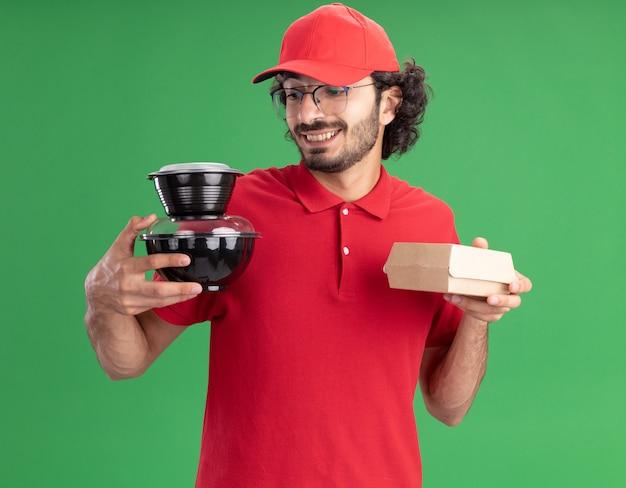 Sorridente giovane fattorino caucasico in uniforme rossa e berretto con gli occhiali che tengono in mano un pacchetto di alimenti di carta e contenitori per alimenti guardando contenitori per alimenti isolati su parete verde