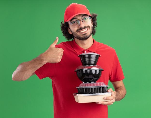 Sorridente giovane fattorino caucasico in uniforme rossa e berretto con gli occhiali che tengono in mano un pacchetto di alimenti di carta e contenitori per alimenti che mostrano il pollice in su