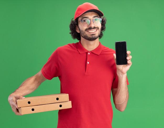 Sorridente giovane fattorino caucasico in uniforme rossa e berretto con gli occhiali che tengono i pacchetti di pizza che mostrano il telefono cellulare