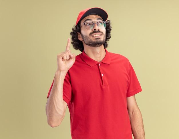 Sorridente giovane fattorino caucasico in uniforme rossa e berretto con gli occhiali guardando il lato rivolto verso l'alto isolato sulla parete verde oliva con spazio di copia