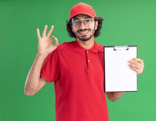 Sorridente giovane fattorino caucasico in uniforme rossa e berretto con gli occhiali che mostra appunti alla fotocamera facendo segno ok con la matita in mano