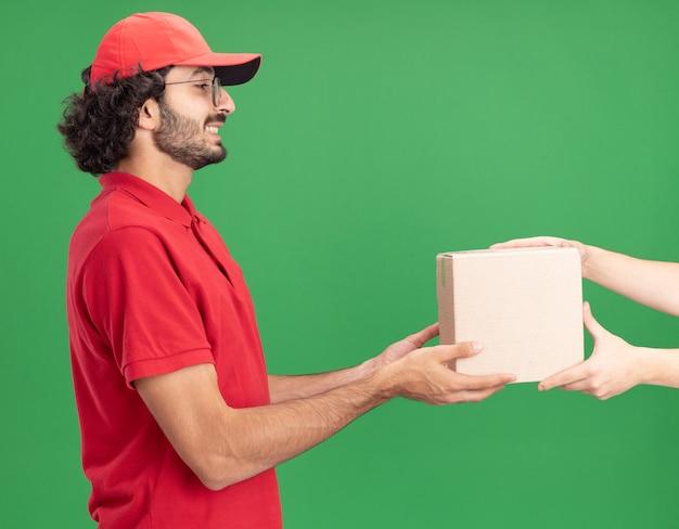 Sorridente giovane fattorino caucasico in uniforme rossa e berretto con gli occhiali in piedi nella vista di profilo che dà una scatola di cartone al cliente che la guarda