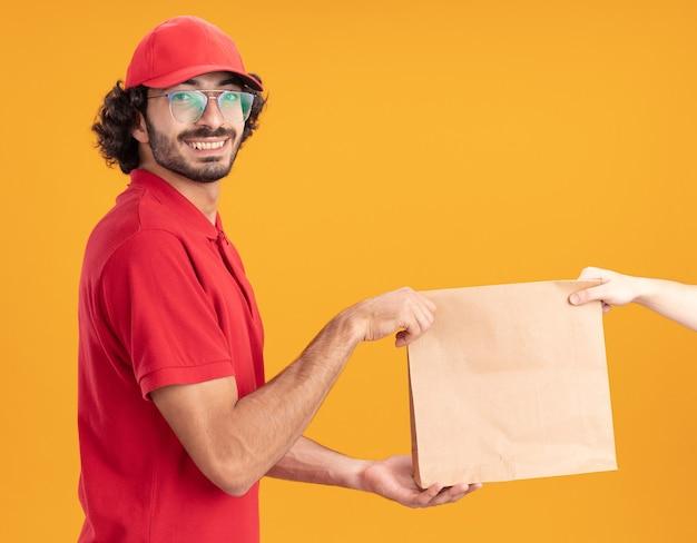 Sorridente giovane fattorino caucasico in uniforme rossa e berretto con gli occhiali in piedi nella vista di profilo che dà il pacchetto di carta al cliente
