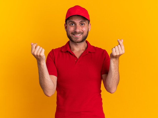 Smiling young caucasian delivery man in uniform and cap doing money gesture