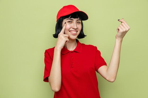 Sorridente giovane donna di consegna caucasica gesticolando soldi