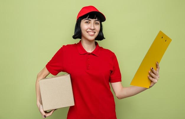 Улыбающаяся молодая кавказская женщина-доставщик, держащая картонную коробку и буфер обмена
