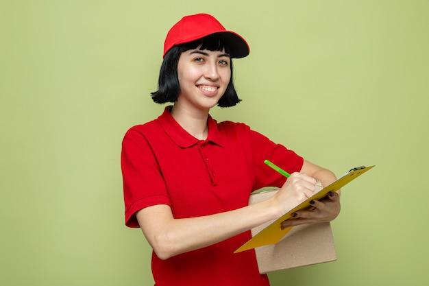 Улыбающаяся молодая кавказская женщина-доставщик, держащая картонную коробку и пишущая в буфере обмена