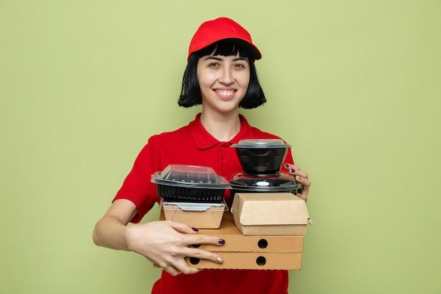 Sorridente giovane donna delle consegne caucasica che tiene in mano contenitori per alimenti e scatole per pizza
