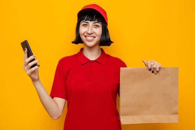 Sorridente giovane donna di consegna caucasica che tiene in mano un sacchetto di carta per alimenti e un telefono