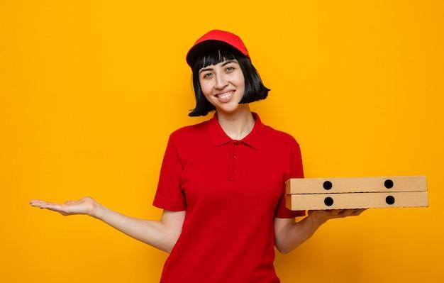 Sorridente giovane donna delle consegne caucasica che tiene in mano scatole per pizza e tiene la mano aperta
