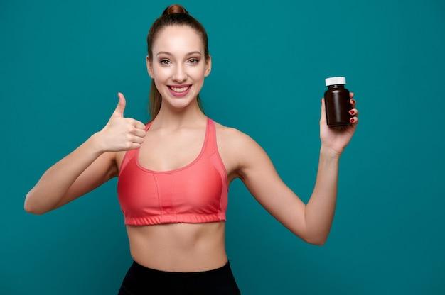 웃는 젊은 백인 여성 피트니스 코치는 병에 약을 들고 엄지손가락을 보여줍니다