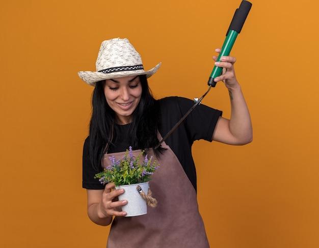 Улыбающаяся молодая кавказская девушка-садовник в униформе и шляпе держит ножницы для живой изгороди и цветочный горшок, глядя на цветы, изолированные на оранжевой стене