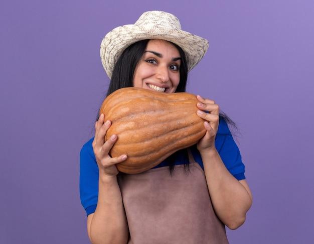 Sorridente giovane giardiniere caucasica ragazza che indossa l'uniforme e cappello che tiene zucca butternut isolata sul muro viola