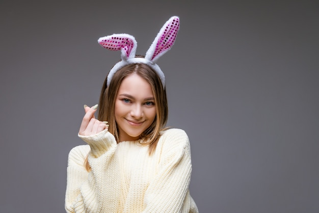 Smiling young caucasian girl, blonde with bunny ears, shows a mini heart with fingers and looking at camera isolated over gray background