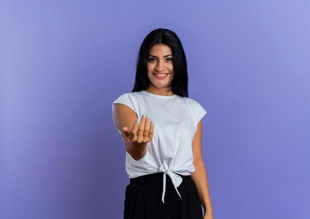 I giovani gesti caucasici sorridenti della ragazza vengono qui segno della mano