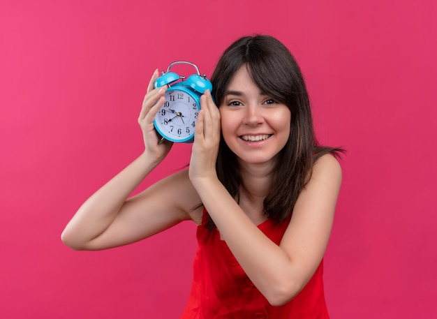 Smiling young caucasian girl holding clock with both hands and looking at camera on isolated pink background