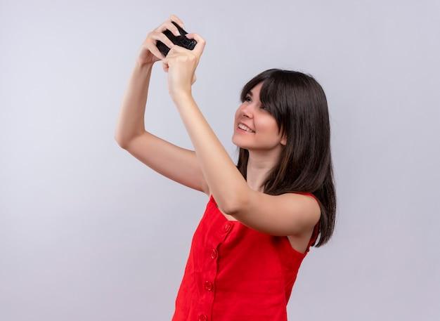 両手で携帯電話を保持し、孤立した白い背景の上の携帯電話を見て笑顔の若い白人の女の子