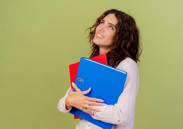 笑顔の若い白人の女の子は見上げるファイルフォルダを保持します