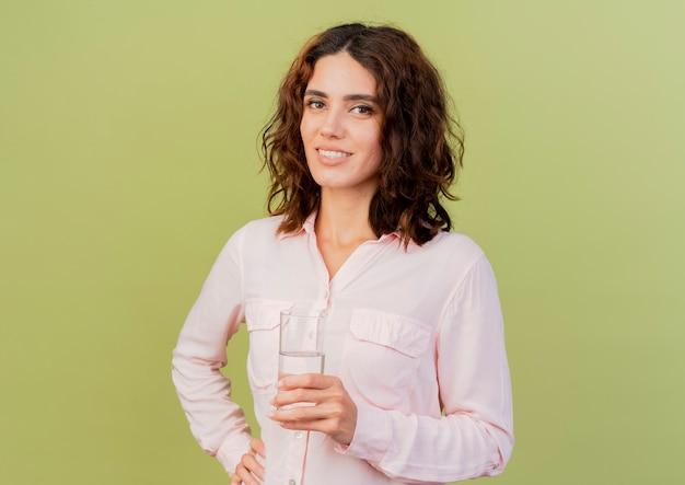 La giovane ragazza caucasica sorridente tiene il bicchiere d'acqua