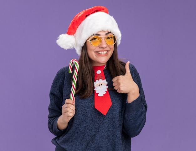 산타 모자와 산타 넥타이와 태양 안경에 웃는 젊은 백인 여자는 사탕 지팡이를 보유하고 복사 공간이 보라색 벽에 고립 된 엄지 손가락