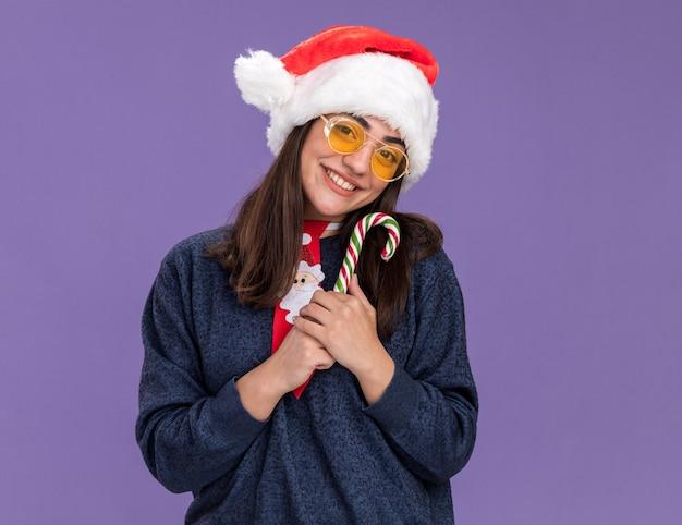 산타 모자와 산타 넥타이와 태양 안경에 웃는 젊은 백인 여자 보유 사탕 지팡이 복사 공간이 보라색 벽에 고립