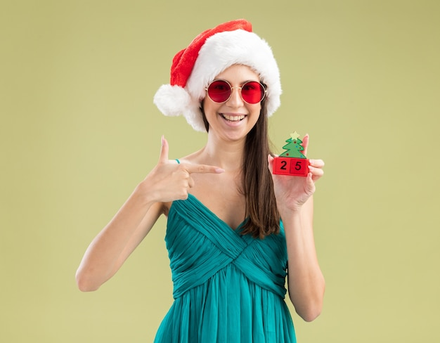 산타 모자를 들고 크리스마스 트리 장식에서 가리키는 태양 안경에 웃는 젊은 백인 여자