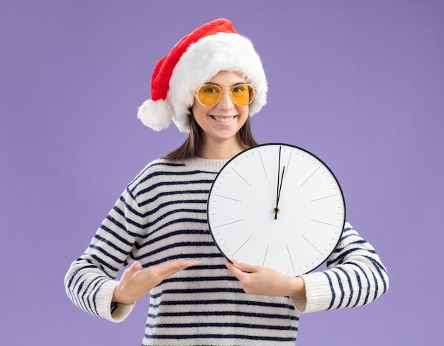 Улыбающаяся молодая кавказская девушка в солнцезащитных очках в шляпе санта-клауса держит и указывает рукой на часы