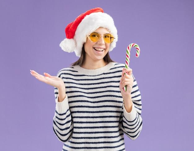 Улыбающаяся молодая кавказская девушка в солнцезащитных очках в шляпе санта-клауса держит конфету и держит руку открытой